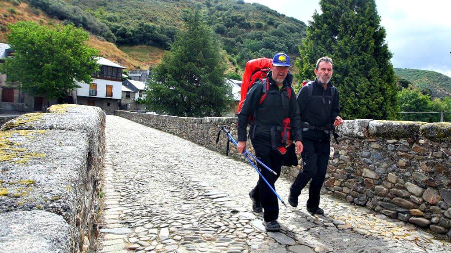 Dos peregrinos cruzando el puente medieval en Molinaseca, León - Camino Francés :: Guía del Camino de Santiago