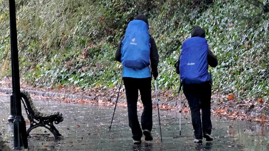 Dos peregrinos bajo la lluvia en el Camino Inglés :: Albergues del Camino de Santiago